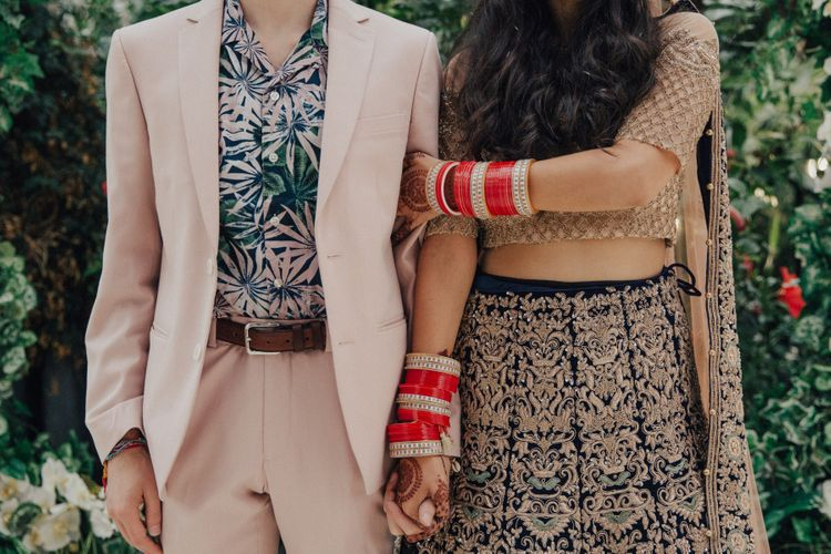 Bride in Gold and Navy Saree and Groom in Beige Suit and Floral Shirt