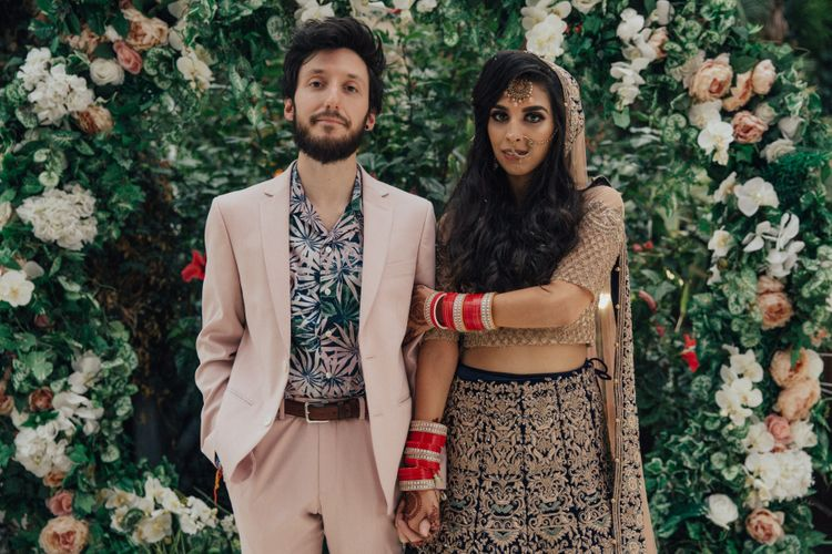 Bride in Gold and Navy Saree and Groom in Beige Suit and Floral Shirt Arm in Arm in Front of Floral moon Gate