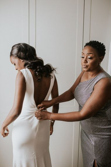 Black bride being helped into her Made With Love Bridal wedding dress