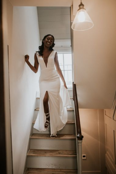 Black bride in Made With Love Bridal gown walking down the stairs