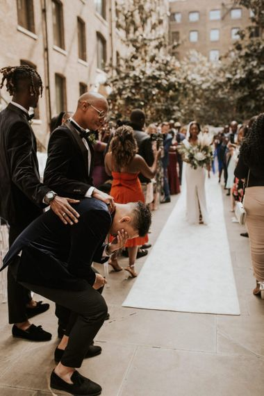 Groom collapsing to his knees as his bride walks down the aisle at Devonshire Terrace wedding ceremony