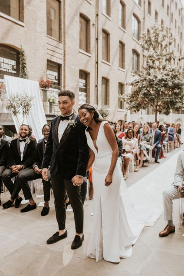Black bride and groom laughing at the altar of their Devonshire Terrace wedding ceremony
