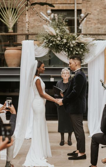 Black bride and groom exchanging vows at their Devonshire Terrace wedding ceremony