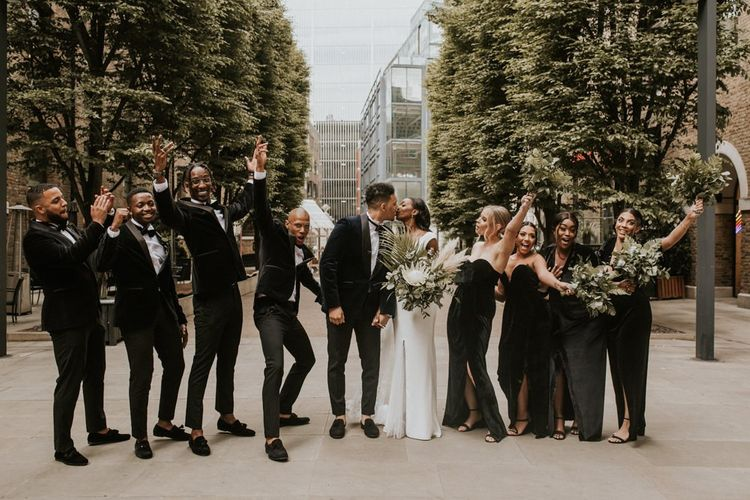 Stylish bridal party portrait in black dresses and tuxedo's