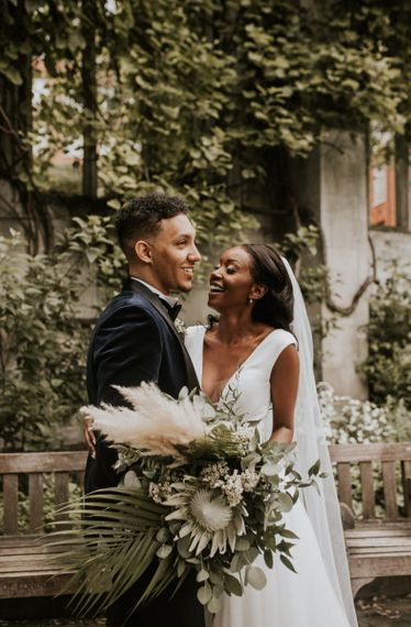 Black bride and groom wedding portrait with king protea, pampas grass and foliage bouquet