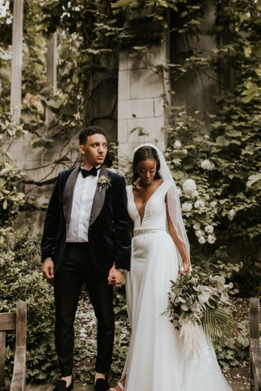 Black bride in Made With Love Bridal gown and groom in velvet dinner jacket and bow tie.