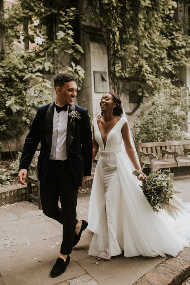 Stylish bride and groom laughing during their St Dunstans in the East wedding portraits
