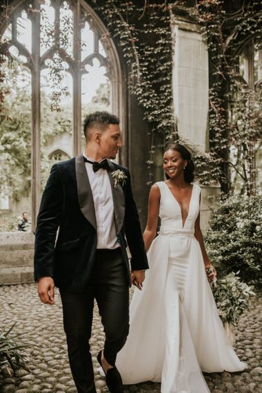 Black bride and groom holding hands at St Dunstans in the East