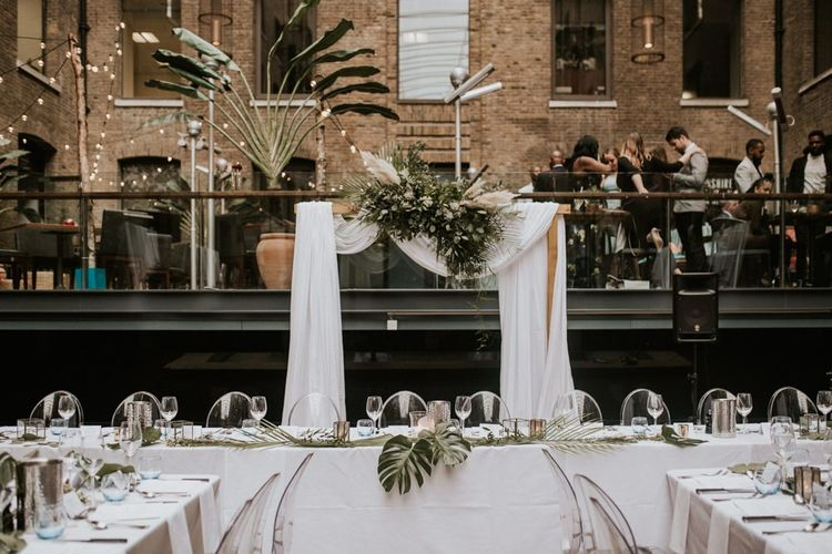 Drapped top table wedding back drop with foliage