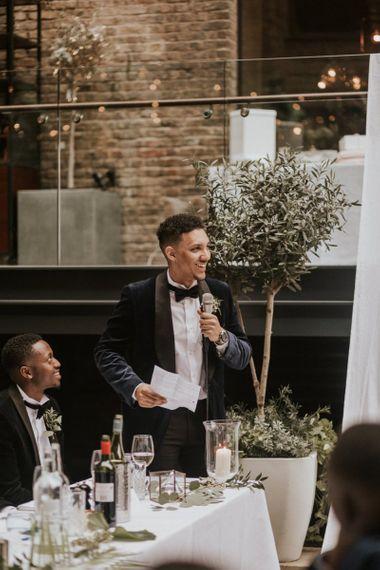 Black groom in Navy Velvet Tuxedo Jacket giving his wedding speech,