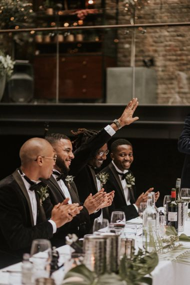 Groomsmen laughing during the wedding reception speeches.