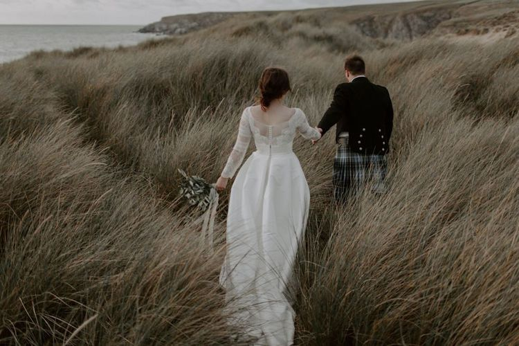 Jesus Peiro Wedding Dress With Groom In Kilt at Holywell Bay
