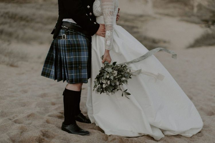 Bride Holds Bouquet And Groom In Kilt for Holywell Bay portraits