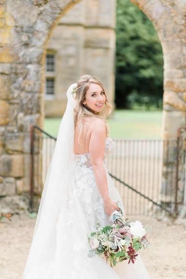 Bride in Strapless Liz Martinez Ballgown Wedding Dress with Embroidered Flowers | Cathedral Length Veil in Blush Soft Tulle | Bridal Bouquet of White Peonies, Blush Astlibe, Trailing Greenery and Burgundy Eucalyptus | Country Tipi Wedding with Macramé Arch and Hanging Flowers | Sarah-Jane Ethan Photography