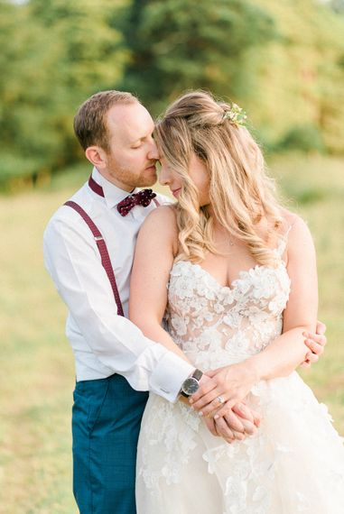 Bride in Strapless Liz Martinez Ballgown Wedding Dress with Embroidered Flowers | Groom in Navy Blue Suit with Burgundy Braces, Bow Tie and Brogues | Country Tipi Wedding with Macramé Arch and Hanging Flowers | Sarah-Jane Ethan Photography