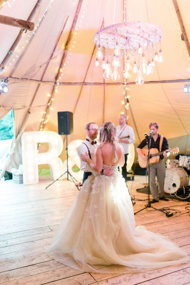 First Dance | Bride in Strapless Liz Martinez Ballgown Wedding Dress with Embroidered Flowers | Groom in Navy Blue Suit with Burgundy Braces, Bow Tie and Brogues | Country Tipi Wedding with Macramé Arch and Hanging Flowers | Sarah-Jane Ethan Photography