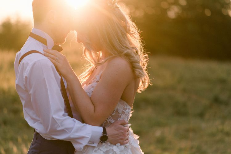 Golden Hour Couples Shot | Bride in Strapless Liz Martinez Ballgown Wedding Dress with Embroidered Flowers | Groom in Navy Blue Suit with Burgundy Braces, Bow Tie and Brogues | Country Tipi Wedding with Macramé Arch and Hanging Flowers | Sarah-Jane Ethan Photography