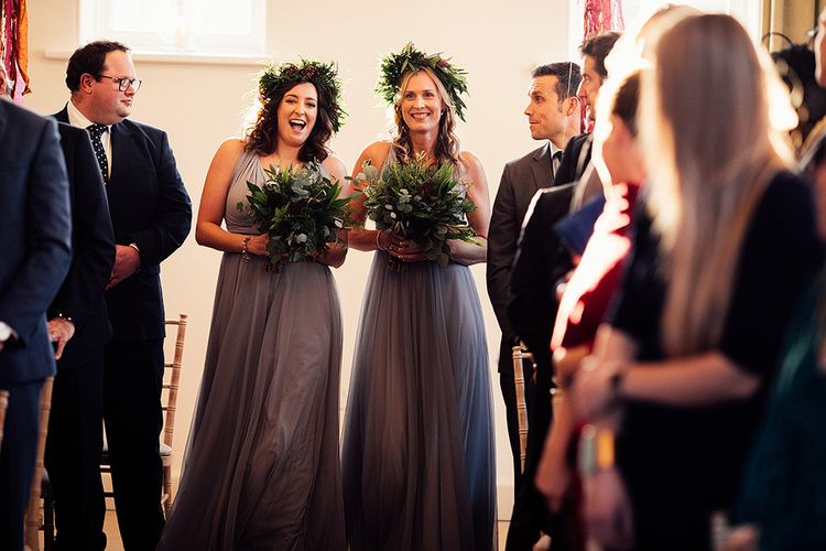 Bridesmaids in grey dresses and foliage crowns walk down the aisle