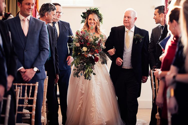 Bride in Riki Dalal wedding dress with foliage crown and large bouquet walks down the aisle
