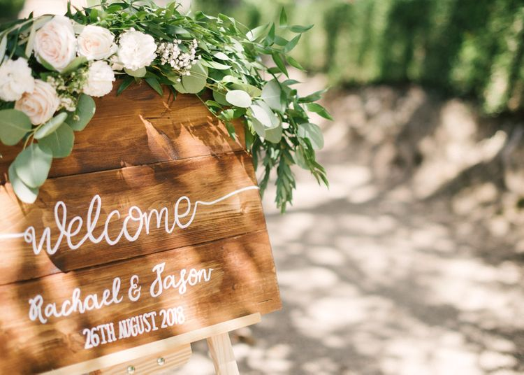Wooden Welcome Sign with Calligraphy Writing and Flowers