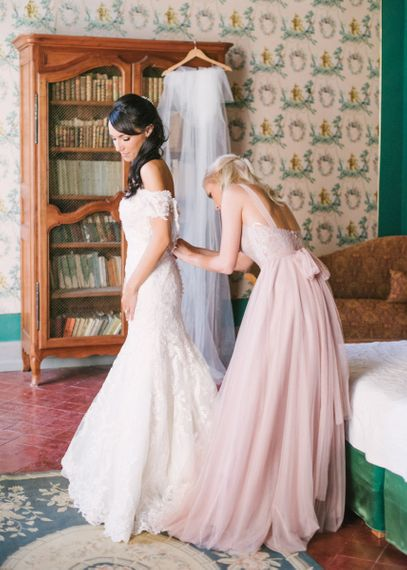 Bridesmaid in Dusky Pink Chiffon Dress Helping Bride into Her Lace David Tutera Wedding Dress