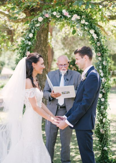 Bride in Lace David Tutera Wedding Dress and Groom in Navy Three Piece Suit Holding Hands During the Outdoor Wedding Ceremony
