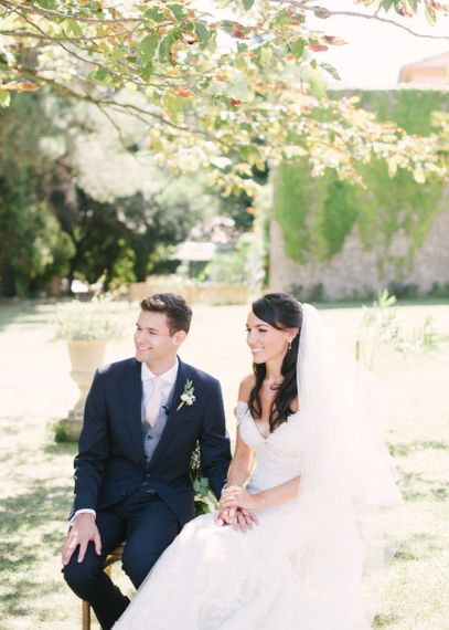Outdoor Wedding Ceremony with Bride in Lace David Tutera Wedding Dress and Groom in Navy Three Piece Suit