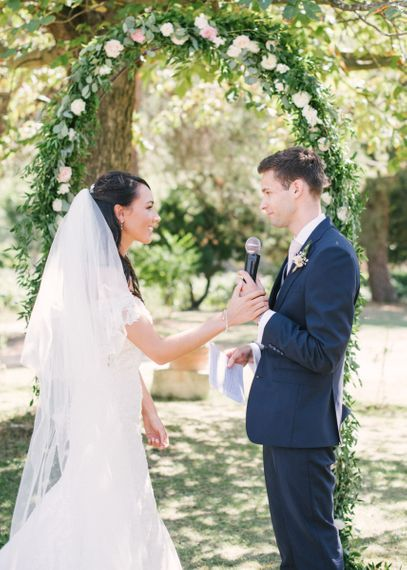 Bride in Lace David Tutera Wedding Dress and Groom in Navy Three Piece Suit  Exchanging Vows