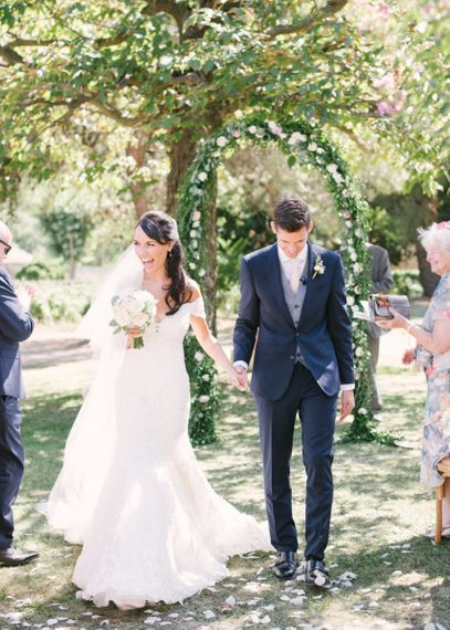 Bride in Lace David Tutera Wedding Dress and Groom in Navy Three Piece Suit Walking Up The Aisle Just Married
