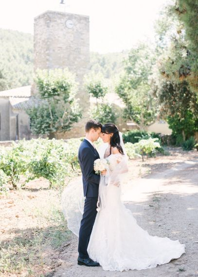 Bride in Lace David Tutera Wedding Dress and Groom in Navy Three Piece Suit Embracing