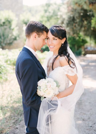 Beautiful Bride in Lace David Tutera Wedding Dress and Groom in Navy Three Piece Suit