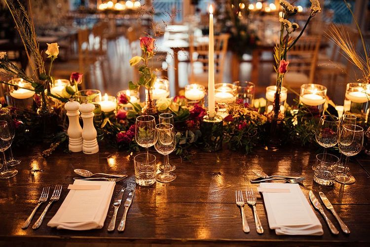 Cosy wedding table decor with candles and flowers