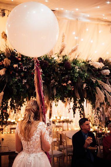 Bride in Riki Dalal wedding dress with tassel balloon and flower installation