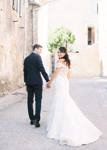 Bride in Lace David Tutera Wedding Dress and Groom in Navy Three Piece Suit Holding Hands