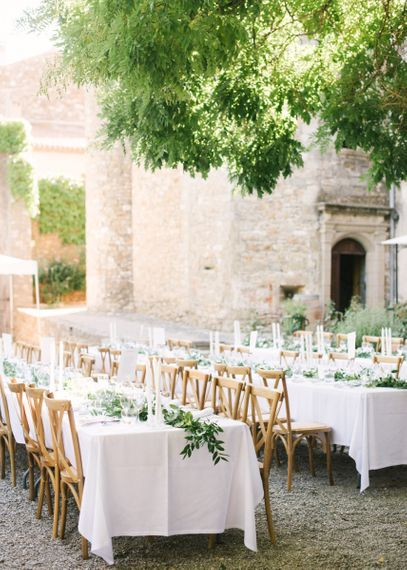 Outdoor Wedding Reception with Wooden Chairs, White Linen and Green Floral Decor