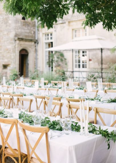 Outdoor Wedding Reception with Wooden Chairs, White Linen and Candles and Green Floral Decor