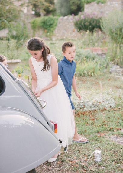 Flower Girl Tying Tin Cans to The Wedding Car