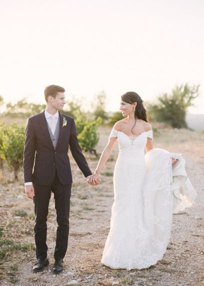 Bride in Lace David Tutera Wedding Dress and Groom in Navy Three Piece Suit  Holding Hands by The Mountains