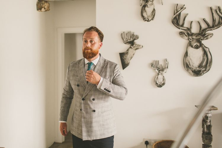 Groom in check suit for rustic wedding with macrame table runner