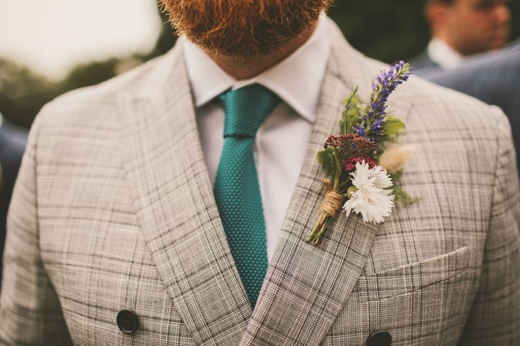 Floral buttonhole, check dinner jacket and green tie for groom