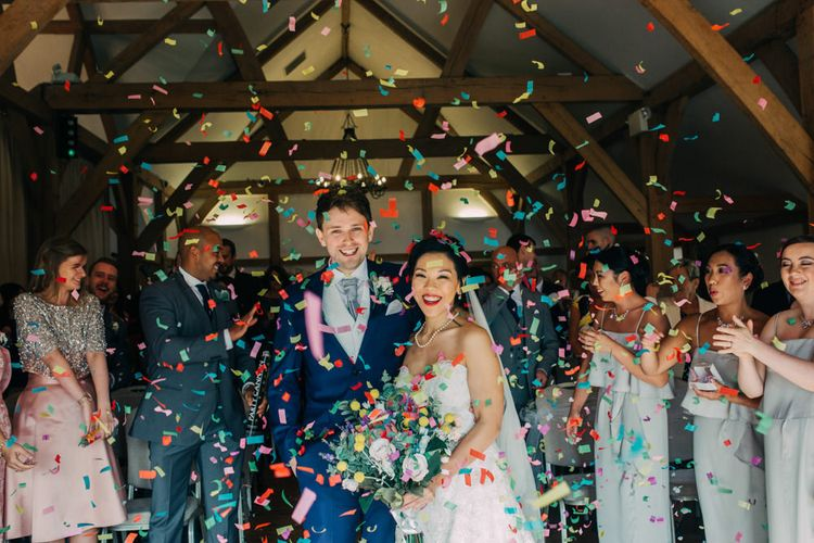 Colourful Confetti Bomb with Bride in Princess Wedding Dress and Groom in Navy Suit