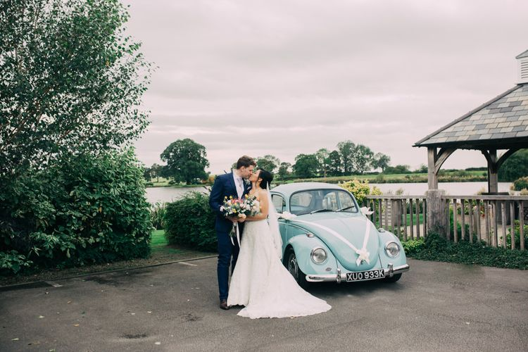 Bride in Off The Shoulder Wedding Dress and Groom in Navy Suit Kissing By Blue VW Beetle Wedding Car