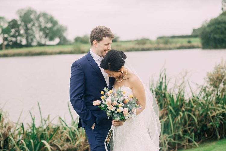 Bride and Groom Portrait by the Lake with Bride in Bandeau Wedding Dress and Groom in Navy Suit