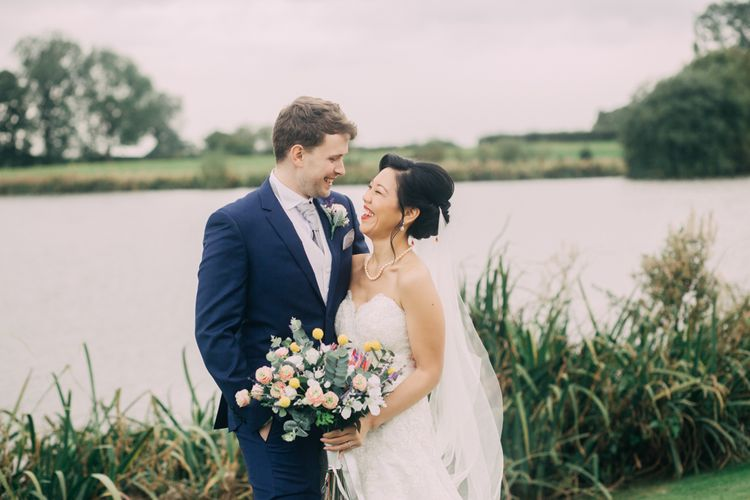 Bride and Groom Portrait by the Lake with Bride in Strapless Wedding Dress and Groom in Navy Suit