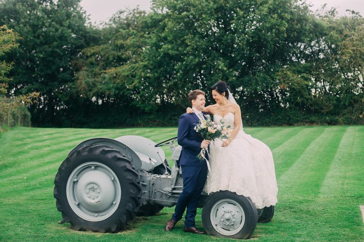 Bride in Princess Wedding Dress and Groom in Navy Suit Sitting on a Tractor