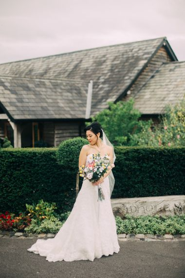 Beautiful Bride in Sweetheart neckline Wedding Dress Holding a Colourful Wedding Bouquet