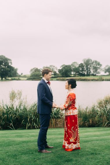Bride in red Chinese wedding dress and groom in Black tuxedo by the lake