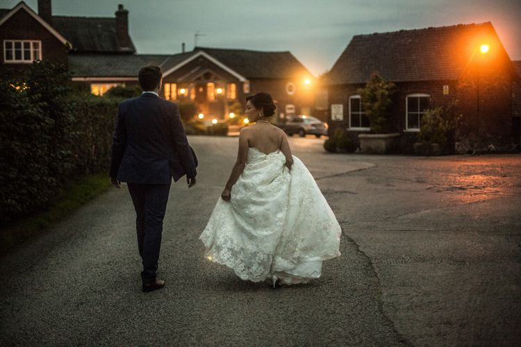 Bride in Lace Off The Shoulder Wedding Dress and Groom in Tuxedo  Walking Down a Country Lane