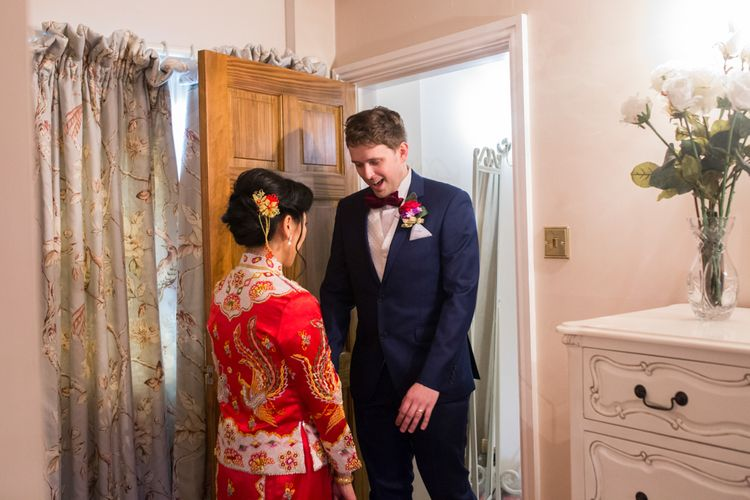 Bride in Red Chinese Wedding Dress Opening Door to Husband-to-be in Tuxedo