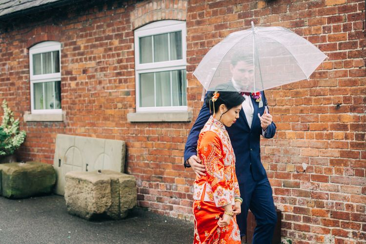 Groom in Black Tuxedo Holding umbrella over bride in red Chinese wedding dress